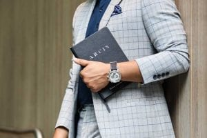 Arcis Man holding journal in a suit and timepiece